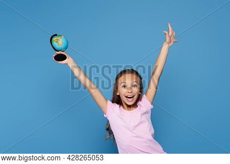Excited Schoolkid Holding Globe And Looking At Camera Isolated On Blue