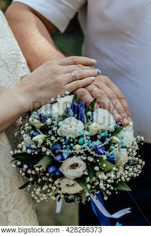 Picture Of Man And Woman With Bridal Bouquet. Married Couple Holding Hands, Ceremony Wedding Day. Ne