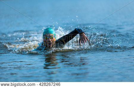 Professional Triathlete Swimming In Rivers Open Water. Man Wearing Swim Equipment Practicing Triathl
