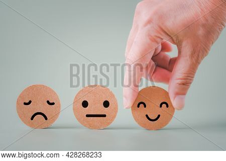 Human's Hand Holding Happy Smile Face On Brown Paper Cut, Satisfaction Survey ,good Feedback Rating
