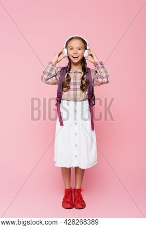 Positive Schoolkid Holding Wireless Headphones On Pink Background