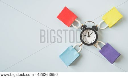 Multi Color Shopping Bags Around Black Analog Alarm Clock With Copy Space, Panorama