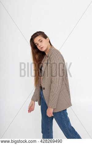 Portrait Of Young Caucasian Attractive Woman With Long Brown Hair In Blue Jeans And Suit Jacket On W