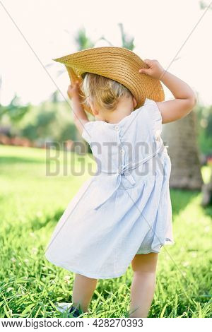 Little Girl Puts On A Hat While Standing On A Green Lawn. Back View