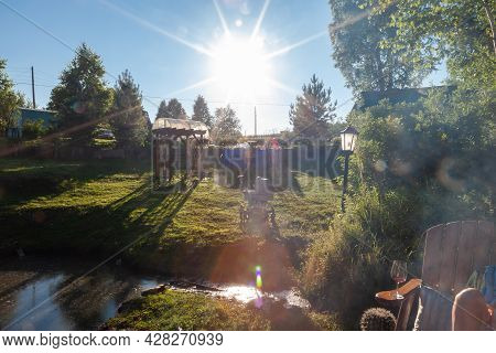 Bright Sunlight In The Garden Of A Country House With A Green Lawn