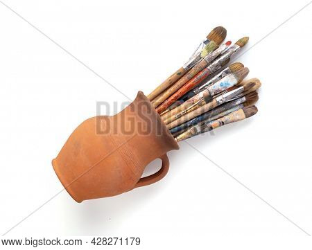 Paint brush in clay jug for art painting isolated on white background. Paintbrush for oil painting as artistic paint still life. Abstract art concept