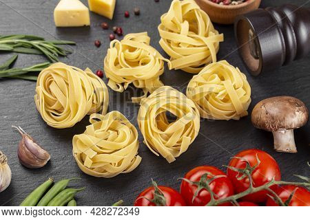 Raw Pasta Tagliatelle With Fresh Tomatoes, Peppers, Asparagus Beans, Spices And Cheese On A Black Ta