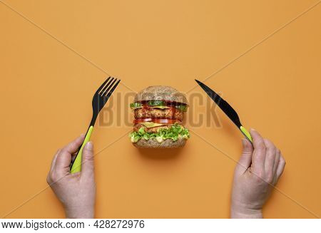 Woman Eating Vegan Burger Top View On A Colored Table. Woman Hands Holding Knife And Fork, Preparing