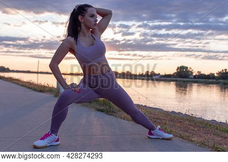 Young Caucasian Woman Stretching Before Running, Warm Up Exercise In Sunrise, Looking Away