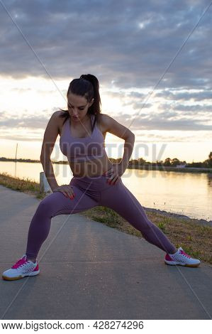 Young Caucasian Woman Stretching Before Running At Riverside, Warm Up Exercise