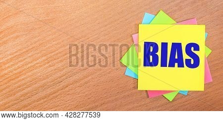 On A Wooden Table, Multi-colored Stickers With The Text Bias. Copy Space