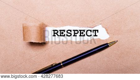 Torn Kraft Paper, White Background With The Text Respect. Nearby Is A Black Handle. View From Above