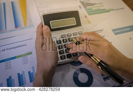 Businessman Or Accountant Hand Holding Pen And Use Calculator To Calculate Income And Loss Statistic