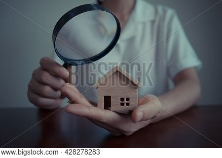 Concepts Of Home Search For Housing Or Home Appraisal. Business Woman Or Bank Officer Using A Magnif