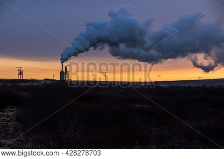 Geothermal Power Station In Iceland. Icelandic Steam During Sunset. Sun Is Shinning Just For A Coupl