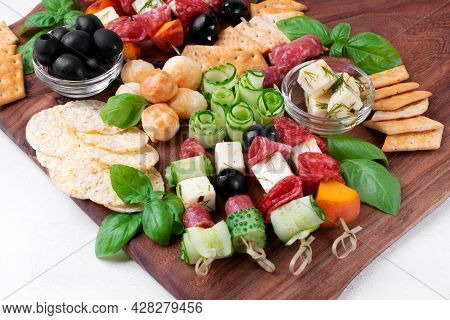Appetizer Assortment On The Wooden Board. Skewer Appetizers, Crackers, Cheese, Cucumber, Salami, Oli