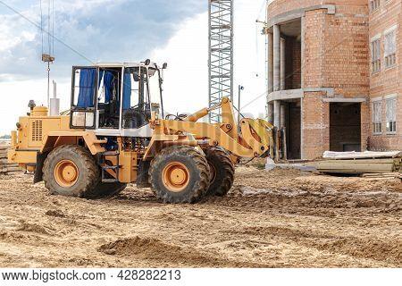 A Forklift At A Construction Site Is Lifting A Reinforced Concrete Slab. Construction Machine. Indus