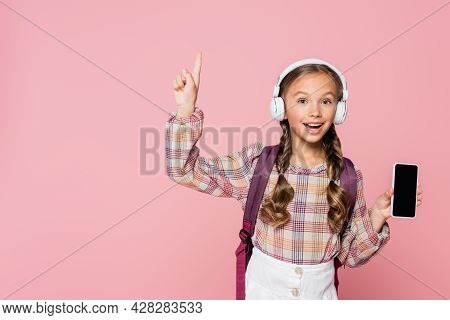 Positive Schoolkid In Headphones Having Idea While Holding Smartphone Isolated On Pink