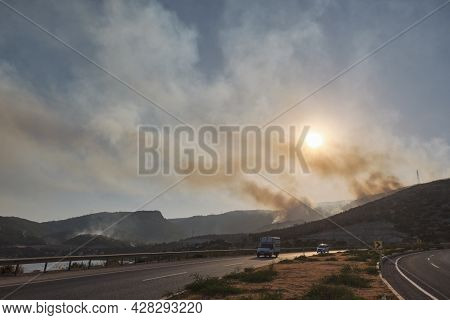 Summer Forest Fires. Smoke Of A Forest Fire Obscures The Sun. Road D400 Antalya - Mersin Against Bur