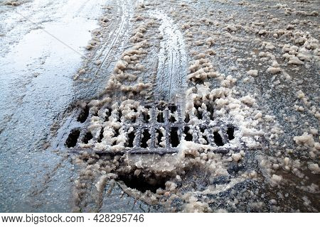 Drain Grate And Pothole On The Road In Winter. Dirty Snow On The Road.