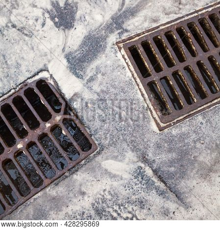 Drain Grates On The Road. Dirty Snow With Sand.