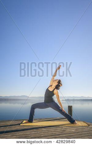 An image of a pretty woman doing yoga at the lake - Parivrtta Parshvakonasana