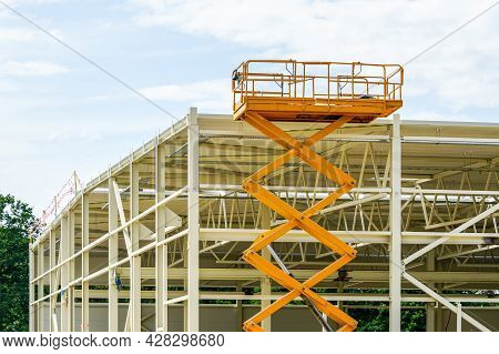 Scissor Lift On The Background Of The Metal Frame Of The Newly Built Factory