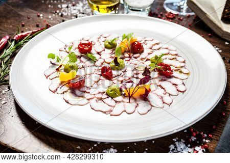 Octopus carpaccio. Spinach cream, cherry tomatoes. Delicious healthy Italian traditional food closeup served for lunch in modern gourmet cuisine restaurant.