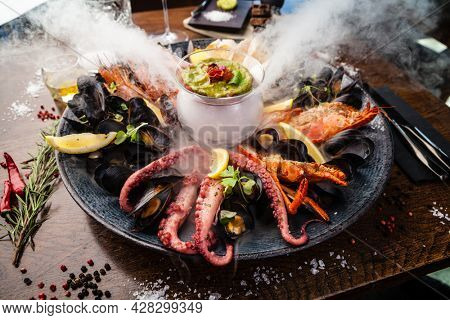Seafood platter for 2-4 persons. Lobster, octopus, blue mussels, Argentina king prawns, tuna tartare. Delicious healthy traditional food closeup served for lunch in modern gourmet cuisine restaurant.