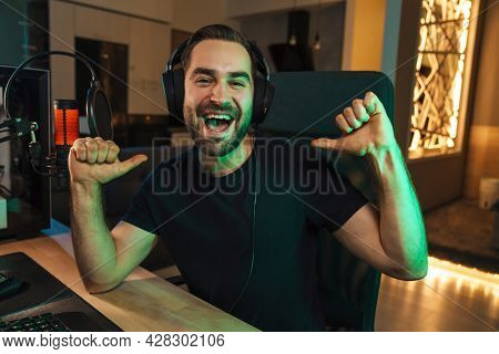 Happy young man gamer streamer in headphones playing on computer talking with players on chat in gaming competition celebrating win