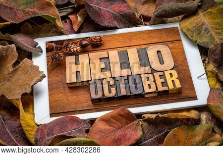 Hello October - word abstract in vintage letterpress wood type blocks on a screen of a digital tablet with colorful dried leaves