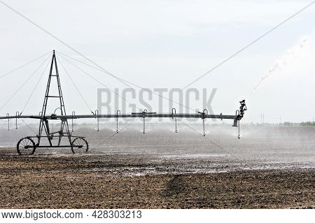 Water Sprinkler, Farming Irrigation System. Automated Agricultural Installation Irrigates Brown Grou