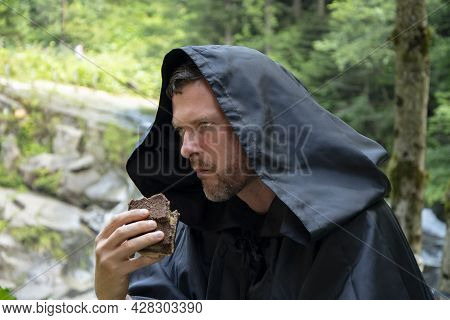 A 35-40-year-old Monk In A Black Cassock With A Hood Eats Bread Against The Background Of A Mountain