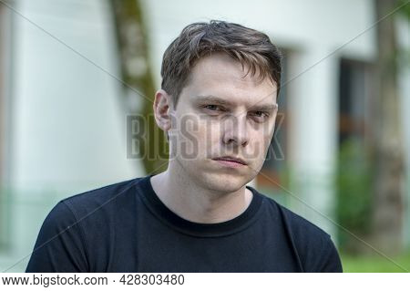 Portrait Of A 35-40-year-old Man In A Black T-shirt On A Blurry Urban Background. Perhaps He Is An I