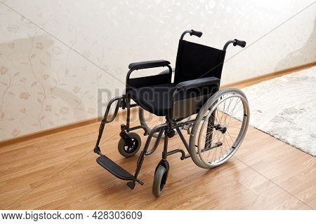 An Empty Wheelchair In Black With Large Wheels And Manual Controls On The Room Background. Barrier-f