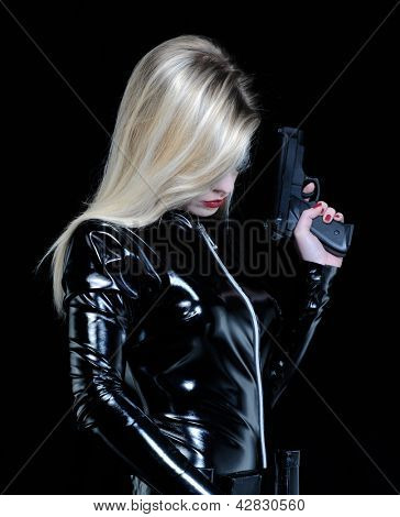 Young blonde woman with black dress holding a gun.