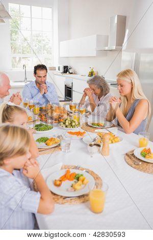 Family praying before eating for thanksgiving