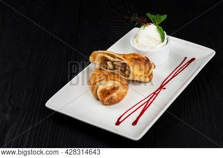 Apple strudel with vanilla ice cream decorated with caramel and berries sauce