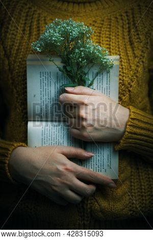 Woman In Sweater Is Holding Book And Bouquet. Open Paper Book And Wildflowers In Arms Of Girl. Warm