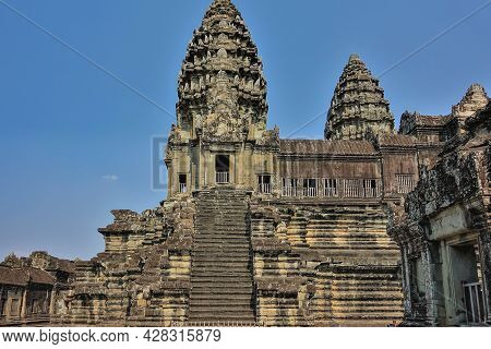 A Fragment Of The Ancient Temple Of Angkor Against The Blue Sky. You Can See A Stone Staircase, Orna