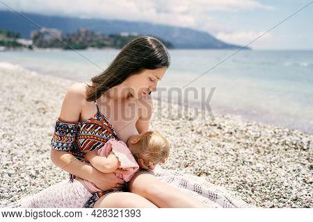 Mom Breastfeeds Little Girl Sitting On Pebble Beach