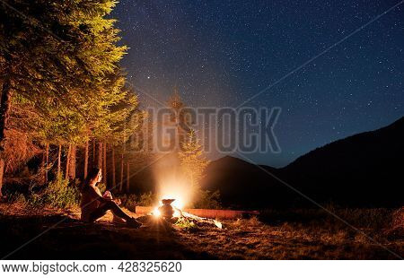 Young Woman Tourist Sitting On Bench Near Campfire Under Magical Sky With Stars. Beautiful View Of N