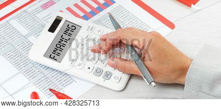 Finance. White Calculator On Financial Graphs On Desk