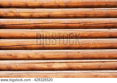 A Wall Of A Rustic Wooden House Made Of Identical Round Brown Logs. The Surface Is Treated With A Pr