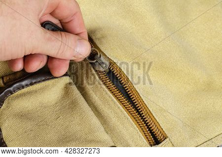 Close-up Of A Man's Hand Closing The Zipper On The Pocket Of A Shoulder Bag. Canvas Casual Bag In Ol