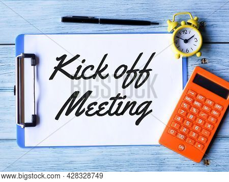 Business Concept. Phrase Kick Off Meeting Written On Paper Clipboard  With A Pen,calculator And Alar