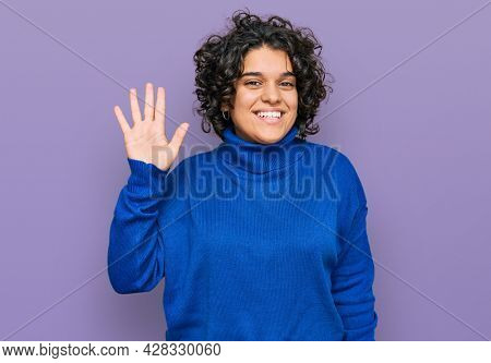 Young hispanic woman with curly hair wearing turtleneck sweater waiving saying hello happy and smiling, friendly welcome gesture