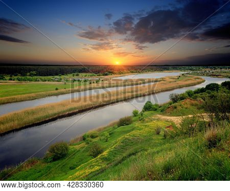 Nice evening sunset landscape over river in forest