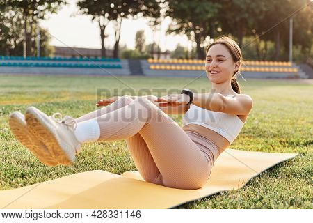 Picture Of Legs And Arms In Process Of Doing Abs. Sportswoman, Wearing Beige Leggings And White Top,