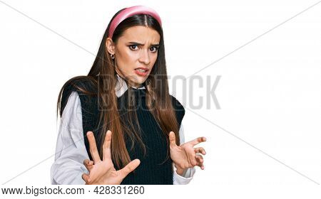 Young beautiful woman wearing casual white shirt disgusted expression, displeased and fearful doing disgust face because aversion reaction. with hands raised